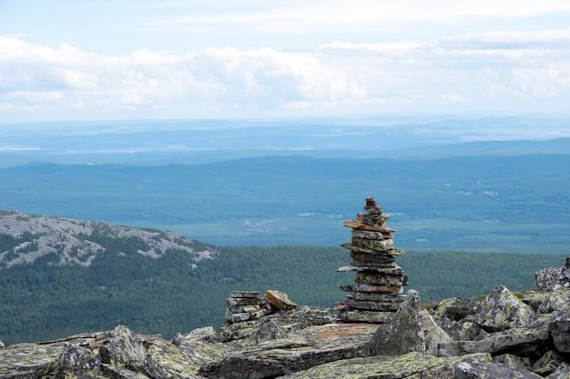 Pietre piramidali impilate che segnano un sentiero di montagna, un punto di riferimento per l'escursionismo, sullo sfondo dei monti urali, russia.