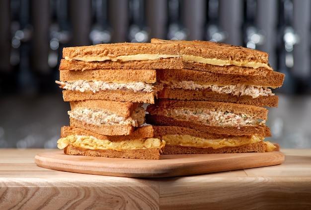 Pila impilata di panini su una lavagna con vari ingredienti.