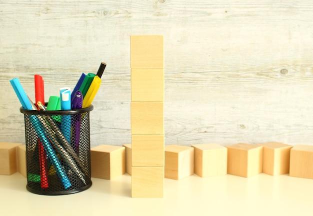 Cubi di legno impilati verticalmente su un tavolo da lavoro bianco su uno sfondo grigio strutturato.