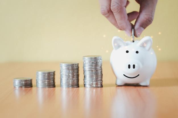 Impilando il mucchio delle monete e mettendo mano moneta nel salvadanaio bianco per risparmiare con i soldi e pianificare un passo in crescita, risparmiare denaro per il fondo pensione e il concetto di piano futuro.