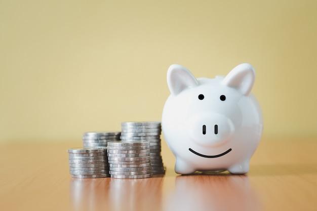 Impilando il mucchio delle monete e il salvadanaio bianco per il risparmio con i soldi e la pianificazione aumentano la crescita, risparmiando denaro per il fondo pensione e il concetto di piano futuro.