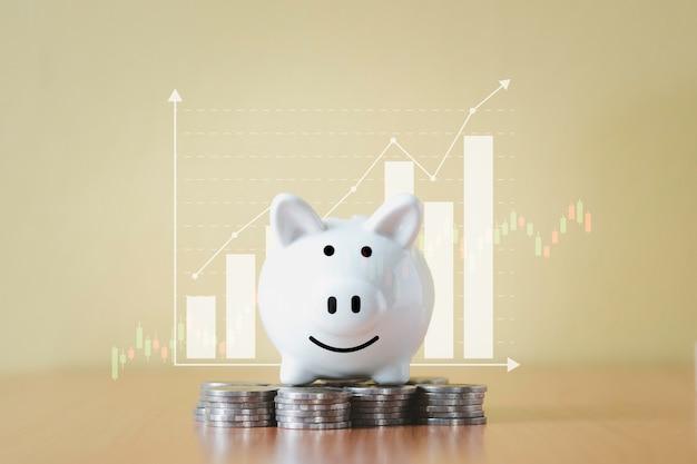 Impilando il mucchio delle monete e il salvadanaio bianco per il risparmio con i soldi e la pianificazione aumentano la crescita con lo sfondo del grafico commerciale, il risparmio di denaro per il fondo pensione e il concetto di piano futuro.