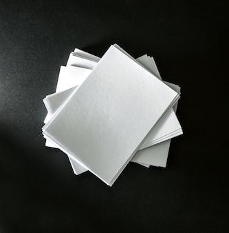 Impilamento del biglietto da visita bianco vuoto del modello su fondo di carta nero