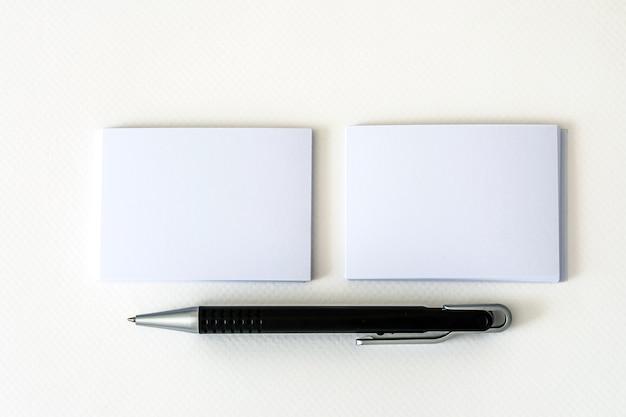 Impilamento del biglietto da visita bianco vuoto di mockup con la penna di eleganza