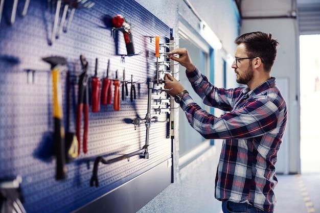 Strumenti di impilamento in officina. un uomo vestito con un abito casual si trova accanto a un pannello portautensili e riordina le chiavi. lavori meccanici interni, riparazione macchine e automobili