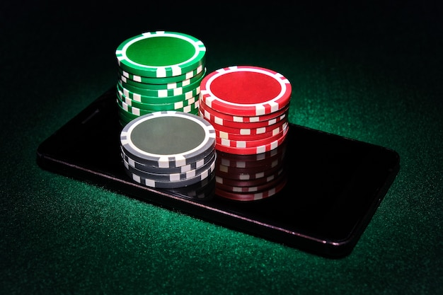 Pile di fiches del casinò su uno smart phone, sfondo tavolo da poker feltro verde. concetto di gioco online.