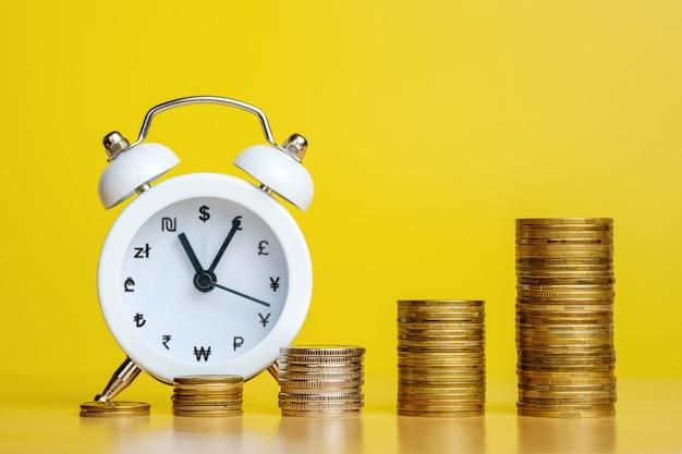 Pile di monete in fila crescente e sveglia con segni di valuta invece di numeri sullo sfondo. il tempo è denaro, affari efficienti, grandi entrate in concetti a breve termine. copia spazio per il testo