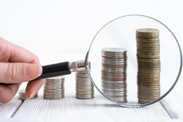 Pile di monete e banconote sfocate sullo sfondo. vista laterale con copia spazio.