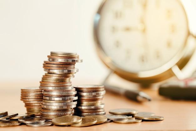 Pile di monete con sveglia di investimento concetto di finanza e denaro aziendale, risparmiare denaro per prepararsi in futuro.