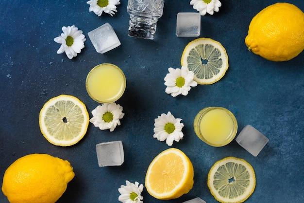 Pile di limoncello fresco con limoni e fiori su sfondo blu