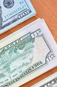 Pile di molte cento e cinquanta banconote in dollari sulla fine di legno della superficie del fondo su. vista dall'alto piatta. concetto astratto di affari