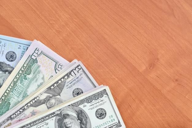Pile di molte cento e cinquanta banconote in dollari sulla fine di legno della superficie del fondo su