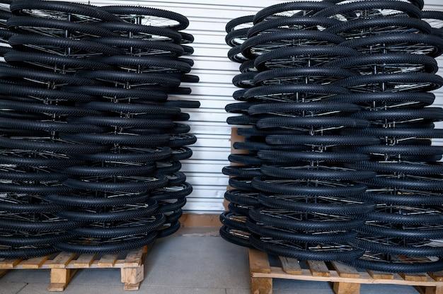Pile di nuove ruote di bicicletta su un pallet, nessuno. negozio di parti di biciclette in fabbrica, pneumatici nell'hangar, file di cerchi e pneumatici per biciclette