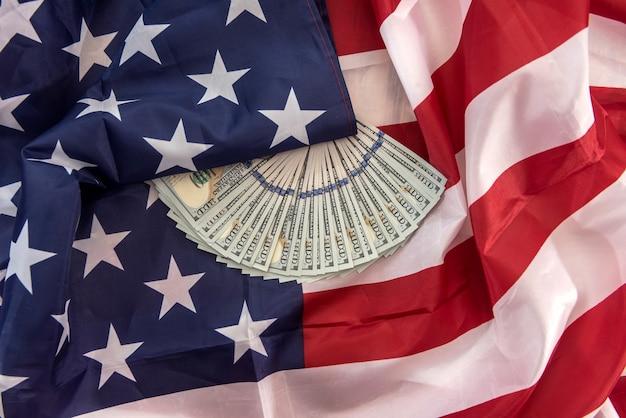 Pile della banconota da cento dollari che giace sulla bandiera americana. salvare il concetto di finanza