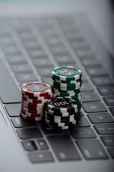 Pile di fiches da poker su un computer portatile. concetto di casinò online.