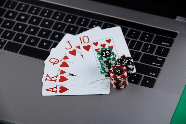 Pile di fiches da poker e carte da gioco su un computer portatile. casinò e poker online concept.