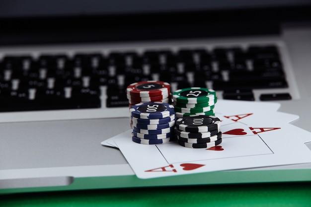 Pile di fiches da poker e carte da gioco su un computer portatile. concetto di casinò online.