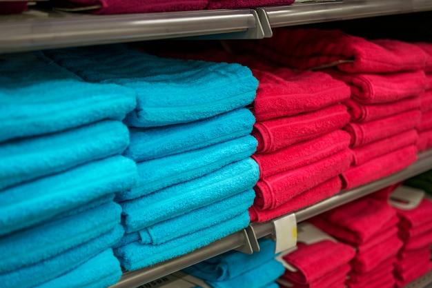 Pile di asciugamani rossi e blu su uno scaffale di un negozio, soft focus