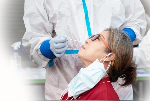 Personale che controlla la donna anziana per il coronavirus usando il metodo del tampone nasale
