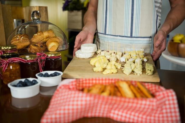 Personale in possesso di vari tipi di formaggi in tavola di legno