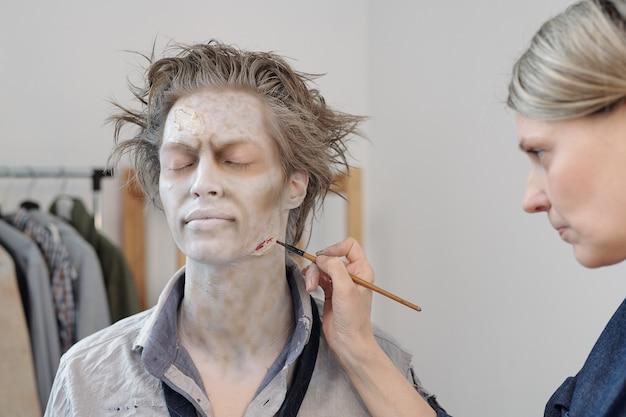 Artista di trucco di scena con pittura a pennello ferita sul viso di un giovane uomo