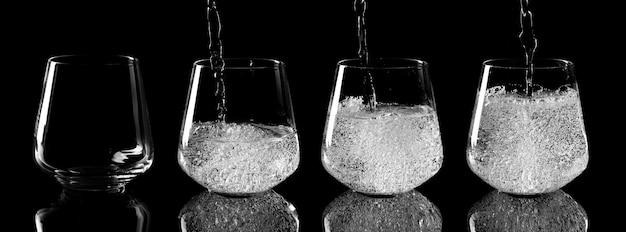 Fasi di versamento dell'acqua nel bicchiere di vetro su sfondo nero