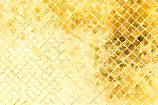 Colore dorato del vetro macchiato luminoso sulla vecchia parete in tempio