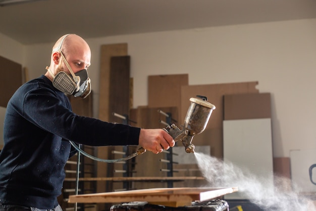 Colorazione di un legno con pistola a spruzzo bianca, applicazione di ritardante di fiamma che garantisce protezione antincendio, dispositivo di spruzzatura airless, concetto industriale