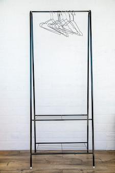 Appendiabiti in acciaio inox con appendiabiti vuoti contro un muro bianco e pavimento in legno.