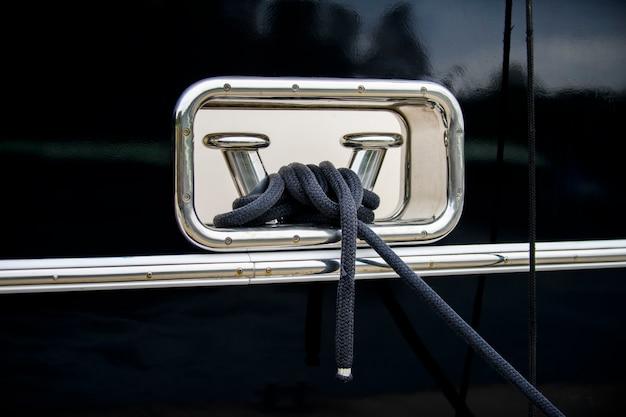 Dissuasore in acciaio inox lucidato con cima di ormeggio sullo scafo blu scuro dello yacht super lusso.