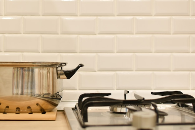 La pentola in acciaio inossidabile si trova accanto al bruciatore a gas contro il muro della cucina in mattoni bianchi. interiore della cucina con fornello a gas e utensili. stoviglie. spazio di lavoro per la cottura dei cibi. stoviglie. spazio per il testo