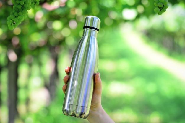 Bottiglia d'acqua riutilizzabile in acciaio inossidabile sullo sfondo del vigneto