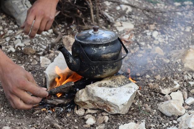 Teiera in acciaio inossidabile su legna da ardere nella scena naturale di montagna durante il picnic