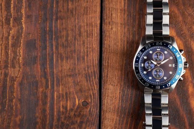 Orologio da polso in acciaio inossidabile con quadrante blu su un tavolo di legno marrone