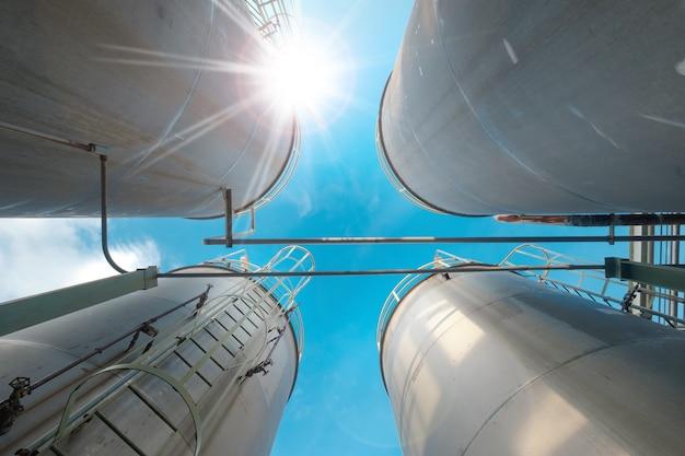 Serbatoi e condutture inossidabili per prodotti chimici liquidi industriali sullo sfondo del cielo blu
