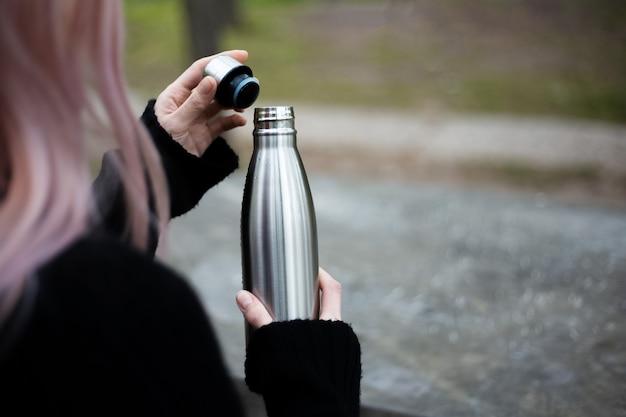Bottiglia termica inox per acqua in mano. Foto Premium