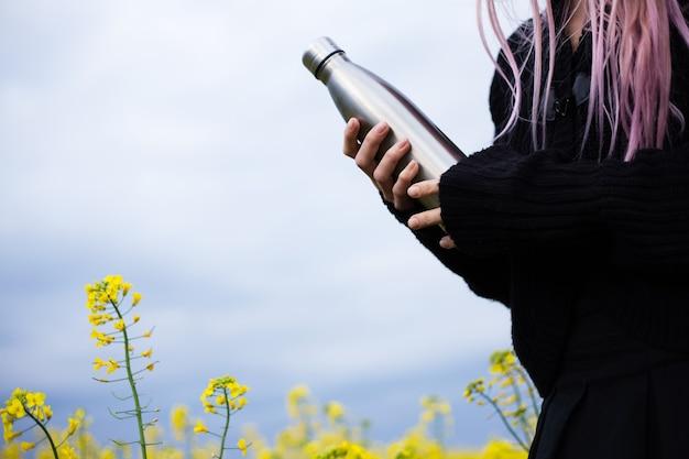 Bottiglia thermos inossidabile in mano, sulla superficie del campo di colza.