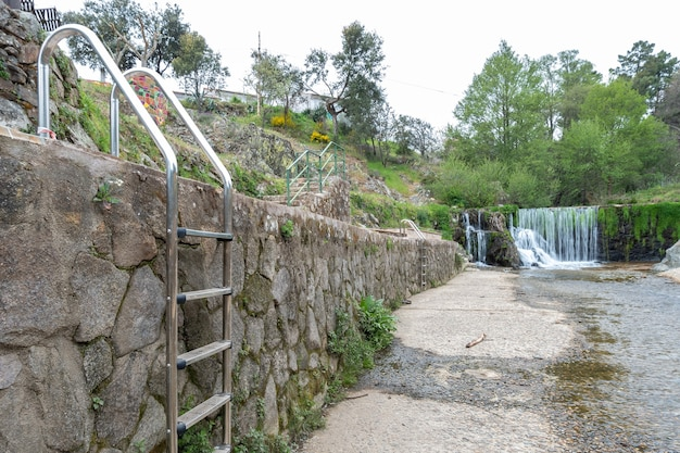 Scale nella piscina naturale che è vuota e sullo sfondo la cascata