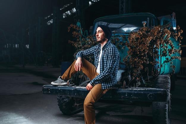 Stalker, viaggiatore da solo posa contro auto abbandonate, interni della vecchia fabbrica
