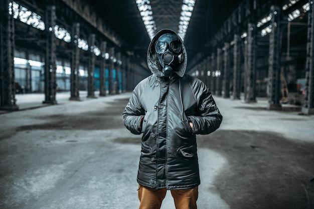 Concetto di stalker, persona di sesso maschile in maschera antigas in edificio abbandonato. stile di vita post apocalittico, giorno del giudizio, orrore della guerra nucleare