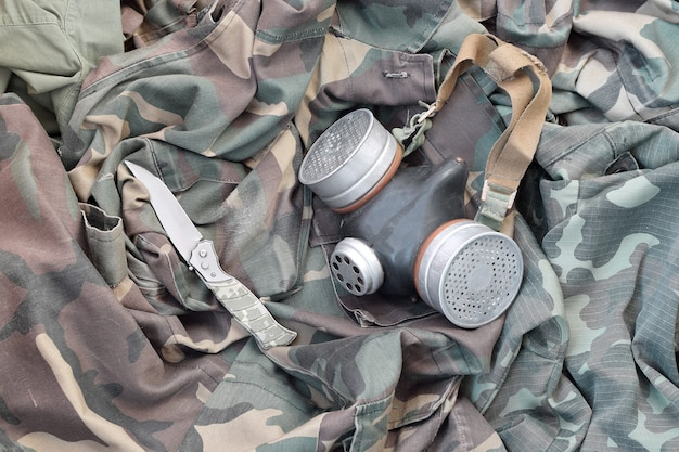 La maschera antigas sovietica dei soldati di stalker si trova con il coltello sulle giacche mimetiche cachi verdi. kit di oggetti sopravvissuti all'apocalisse post