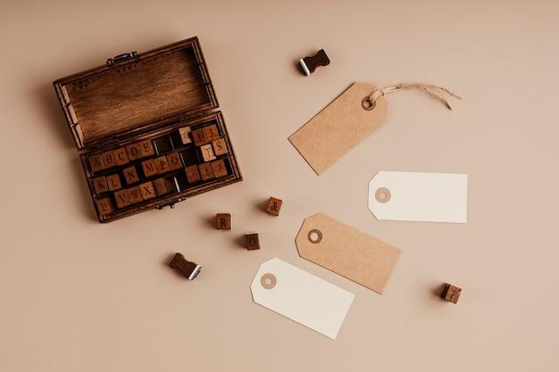 Timbro alfabeto e tag regalo su sfondo beige. idea artigianale, fai da te, hobby. disposizione piatta, vista dall'alto