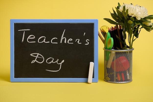 Un supporto per penne e matite sul desktop su uno sfondo giallo con spazio di copia. supporto con materiale scolastico colorato e fiore di aster e lavagna con scritta teacher's day