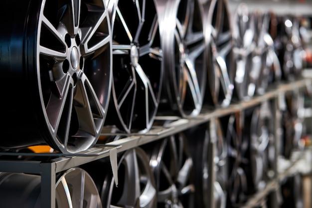Stand con ruote in lega nel moderno negozio di pneumatici, foto ravvicinata di ruote auto nel negozio di servizi auto