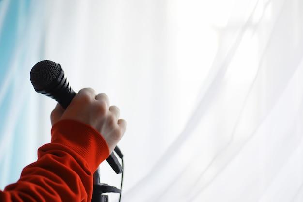 Stai in piedi con un microfono. l'uomo tiene per mano un microfono su un treppiede. performance dell'artista con un microfono. scena con un microfono.