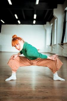 In piedi in asana. allenatore di yoga sottile di bell'aspetto con un dolcevita verde che sembra concentrato mentre si trova in asana