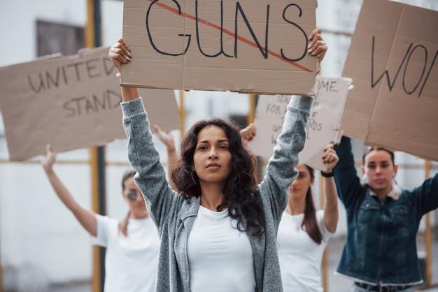 In piedi alla dimostrazione. un gruppo di donne femministe protesta per i loro diritti all'aperto