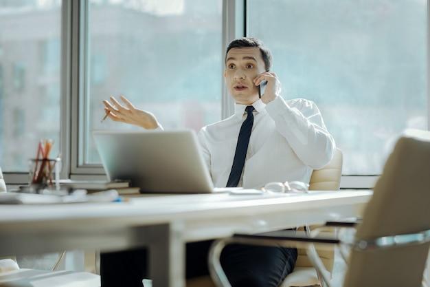 Stare in piedi. piacevole giovane uomo d'affari seduto davanti al laptop nel suo ufficio e parlando emotivamente a qualcuno al telefono, obiettando alla loro opinione