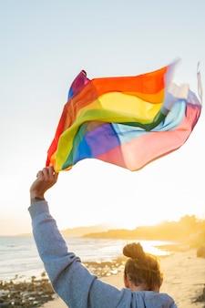 L'uomo in piedi ha alzato al cielo la bandiera arcobaleno lgbt