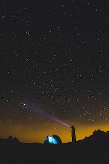 Uomo in piedi con la luce della torcia che guarda la galassia notturna dello spazio nero e goditi l'attività di svago all'aperto in viaggi di vacanza alternativi